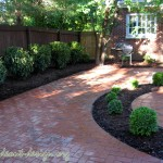 The brick patio with a circular center detail of boxwoods and a cast stone urn.