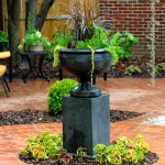 Clay brick pavers with a large cast stone container as the focal point.