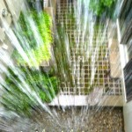 Rain pours from the second story custom gutter system to the pea gravel below which filters into an underground