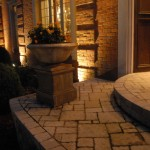 Porch with natural stone veneer and paver curved step detail, cast stone containers, and lighting